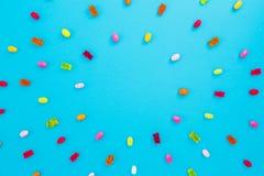 色的糖果圆的框架在蓝色背景的 平的位置,顶视图 图库摄影