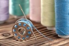 色的缝合针线和片盘在木背景 免版税图库摄影