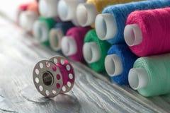 色的缝合针线和片盘在木背景 库存图片