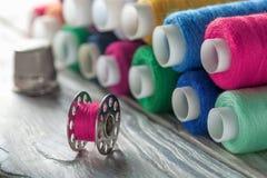 色的缝合针线和片盘在木背景 免版税库存图片
