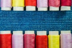 色的缝合针线短管轴在蓝色牛仔布的两行安排了与拷贝空间 免版税库存照片