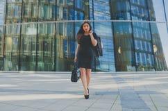 黑色的美丽的女孩与一个袋子在手中在商业中心的背景 库存图片