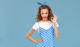 色的蓝色背景的美丽的滑稽的女孩 库存照片