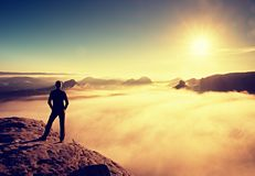 黑色的远足者在岩石在破晓内的abve谷和手表站立对太阳 美好的片刻自然奇迹  库存照片