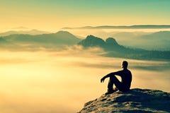 黑色的远足者在岩石峰顶 在山的美妙的破晓,在谷的重的橙色薄雾 人坐岩石 免版税库存照片
