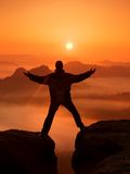 黑色的远足者庆祝在两个岩石峰顶之间的胜利 在落矶山脉的美妙的破晓,在深谷的重的橙色薄雾 免版税库存图片