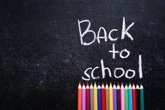 色的铅笔下回到在板岩黑色背景的学校词 回到概念学校 顶视图 空位 免版税库存图片