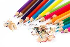 色的铅笔和削片与铅笔 铅笔磨削器在白色背景的 免版税库存图片