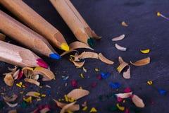 色的铅笔和削片反对黑背景 免版税库存图片