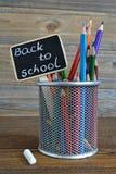 色的铅笔和回到在黑板写的学校课文 免版税库存照片