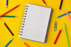 色的铅笔和方格纸笔记关于黄色背景 库存照片