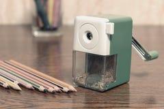 色的铅笔和转台式铅笔刀在桌上,葡萄酒定调子 免版税库存图片