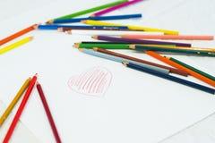 色的铅笔在一张白色纸片说谎与心脏的 图库摄影