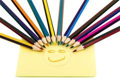 从色的铅笔的面带笑容和与一张被绘的面孔的一个黄色贴纸 免版税库存照片