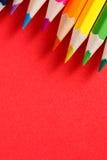 色的铅笔角度 在红色背景的许多不同的色的铅笔 库存照片