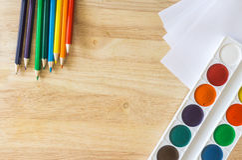 色的铅笔,说谎象彩虹、纸和水彩在木背景 免版税库存图片