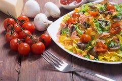 色的面团用蘑菇、蕃茄和乳酪 免版税库存照片