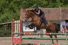 黑色的年轻女骑士跳一匹棕色马 库存图片