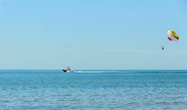 色的parasail翼乘在海水,帆伞运动的一条小船拉扯了 库存照片