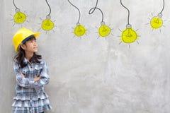 黄色盔甲的女孩有电灯泡想法 免版税库存照片