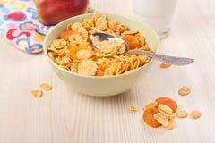 绿色碗嘎吱咬嚼的玉米片早餐用苹果 库存图片