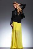 黄色礼服和皮夹克的年轻白肤金发的妇女 免版税库存图片
