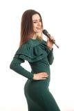 绿色礼服唱歌歌曲的可爱的少妇 图库摄影