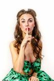 绿色礼服的女孩投入了手指到她的嘴唇 免版税库存图片