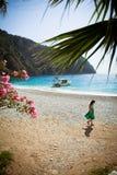绿色礼服的女孩漫步海滩 库存照片
