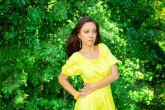 黄色礼服的妇女在森林里expectat的概念 免版税库存照片