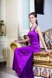 紫色礼服的妇女在豪华内部 库存照片