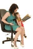 绿色礼服的孕妇读了给孩子 免版税库存图片