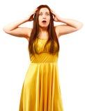 黄色礼服的惊奇的妇女有拿着头的开放嘴的 免版税库存图片