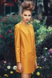 黄色礼服的美丽的女孩有在花背景的卷发的 图库摄影
