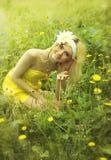 黄色礼服的美丽的妇女坐草。 免版税库存图片