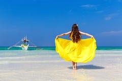 黄色礼服的美丽的深色的妇女有她的回到vi 免版税库存图片