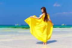 黄色礼服的美丽的深色的妇女有她的回到vi 免版税库存照片