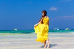 黄色礼服的美丽的深色的妇女有她的回到vi 库存图片