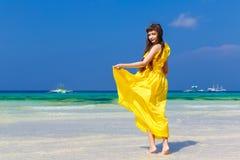黄色礼服的美丽的深色的妇女有她的回到vi 免版税图库摄影