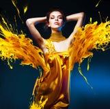 黄色礼服的肉欲的可爱的妇女 免版税库存图片