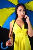 黄色礼服的迷人的妇女有一把时髦的伞的 免版税库存图片