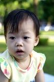 黄色礼服的逗人喜爱的亚裔婴孩在公园 图库摄影