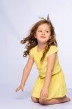 黄色礼服笑的嬉戏的小女孩 免版税库存照片
