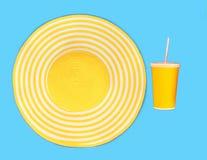 黄色秸杆海滩帽子和杯子汁液在蓝色背景 免版税库存图片