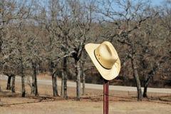 黄色秸杆牛仔帽垂悬生锈的篱芭岗位 免版税库存照片