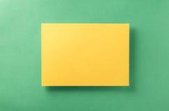 黄色空白的纸片浅绿色的背景 免版税库存图片