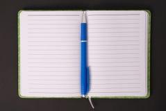 绿色笔记本和蓝色把柄 库存图片