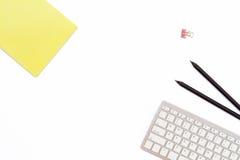 黄色笔记薄、键盘、两黑铅笔和一个夹子纸的在白色背景 最小的运转的概念办公桌 免版税库存图片