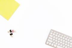 黄色笔记薄、键盘和夹子纸的在白色背景 桌面的最小的企业概念在办公室 免版税图库摄影