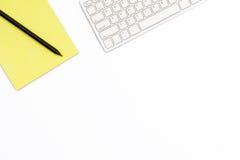 黄色笔记薄、键盘和黑铅笔在白色背景 工作地点的最小的企业概念在办公室 免版税库存图片